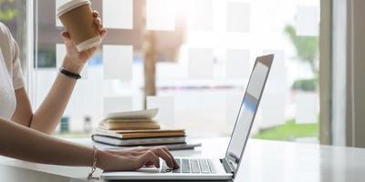 Female employee using laptop at workplace photo