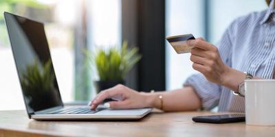 mujer que usa la computadora y que sostiene la tarjeta de crédito para compras en línea foto
