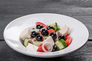 Fresh delicious Greek salad with tomato, cucumber, onions and olives with olive oil photo