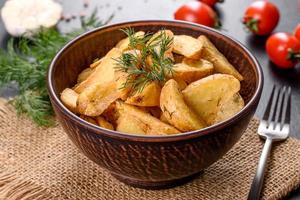 Tasty baked potatoes in a rustic way with spices and herbs in a brown deep plate photo