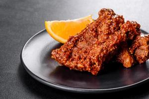 Delicious fresh baked pork ribs with orange on a black plate photo