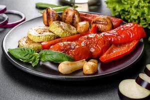 sabrosa parrilla de verduras frescas. tomates, pimientos, champiñones, calabacines y cebollas en una placa negra foto