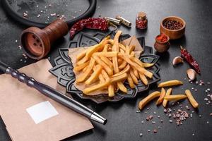 Sabrosas patatas fritas con sal y especias sobre un fondo oscuro foto