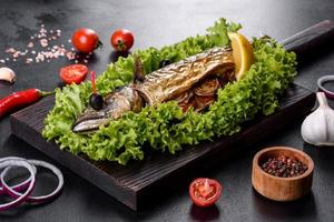Baked mackerel with vegetables on a wooden board with lemon photo