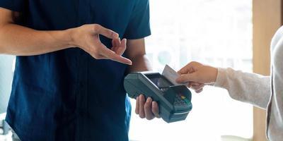 Cerca de la mano del cliente pagando con tarjeta de crédito foto
