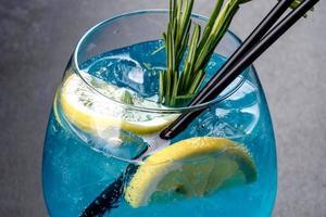 Cóctel alcohólico curacao azul con hielo, limón y tubos de cóctel foto
