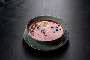 deliciosa sopa caliente fresca con tomate y carne en un plato de cerámica. sopa de mezcolanza foto