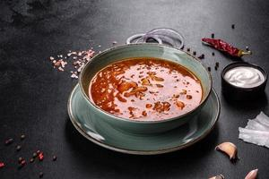 Delicious fresh hot borsch with tomato and meat in a ceramic plate photo