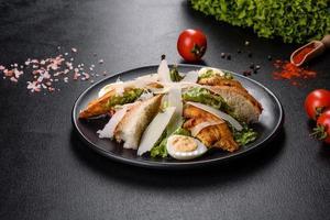 deliciosa ensalada César fresca con carne de pollo, pan rallado, tomates y hojas de lechuga foto