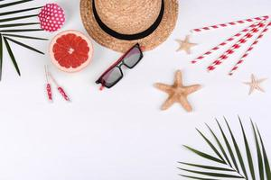 Beach accessories, glasses and hat with shells and sea stars on a colored background photo