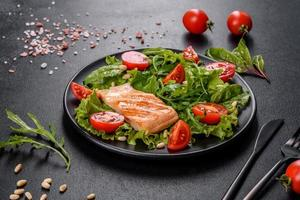 Delicious fresh salad with fish, tomatoes and lettuce leaves photo