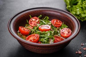 Pieces of chicken, tomatoes and lettuce leaves on a dark concrete background photo