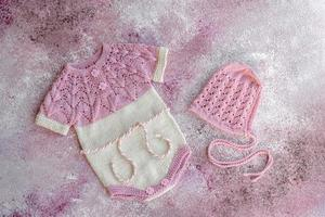 Knitted clothes made of natural wool threads for a newborn baby photo