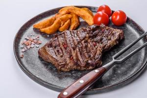 Delicious juicy fresh beef steak with spices and herbs on a white background photo