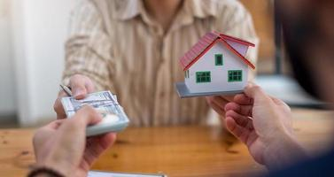 persona entregando dólares con modelo de casa decorativa foto