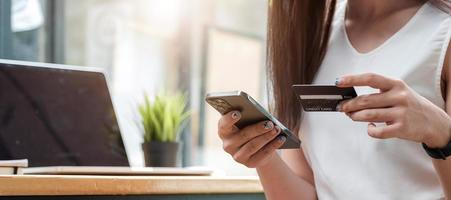 Close up of a woman with smartphone and credit card photo
