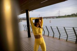 Young woman stretching on the riverside photo