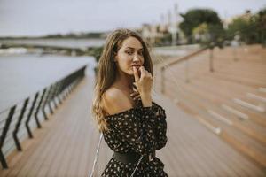 Joven mujer morena de pelo largo caminando por la orilla del río foto