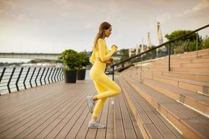Young woman running on the stairs at the riverside photo