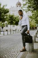 Young African American businessman waitng a taxi on a street photo