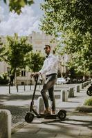 Young African American using electric scooter on a street photo