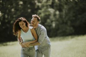 Afectuosa pareja joven divirtiéndose en la hierba verde foto