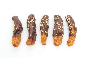 Recubrimiento de chocolate con plátano secado al sol solar o chocolate bañado en plátano aislado sobre fondo blanco. foto