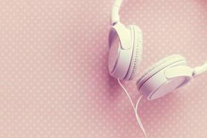 White headphones on pink background photo