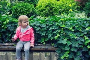 Little girl sitting in the garden, sitting on the bench eating candy photo