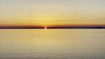 Sunset view over the sea, a kayak floats in the sea, footage video