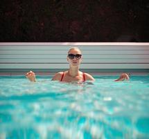 Joven hermosa chica sexy disfrutando de nadar en la piscina privada y relajarse bajo el sol foto