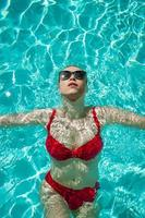 Young beautiful sexy girl enjoying swimming in the private pool and relaxing in the sun photo