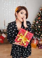 tiroteo navideño. hermosa modelo con regalos de año nuevo en el fondo de un árbol de Navidad. foto