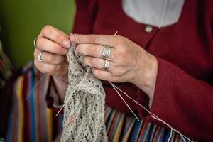 Cerca de las manos de una anciana tejiendo. - imagen foto
