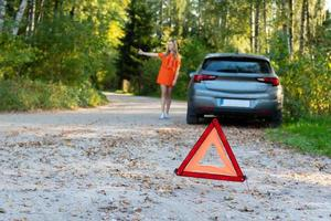 Stressful young woman driver hitchhikes and stops cars, asks for help as have problem with brocken car, uses red triangle sign to warn drivers about stop photo