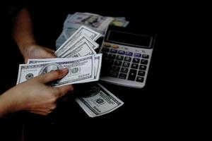 women hand counting money on a stack of 100 US dollars banknotes lots of money photo