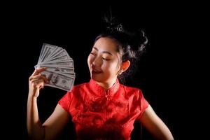 Portrait Asian woman red dress traditional cheongsam holding money 100 Us dollar bills at the black background photo