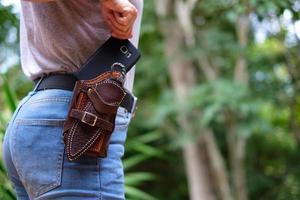 la mujer saca un teléfono inteligente de un cinturón en su cintura foto