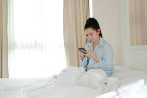 Las mujeres asiáticas usan teléfonos inteligentes en una cama en el dormitorio. foto