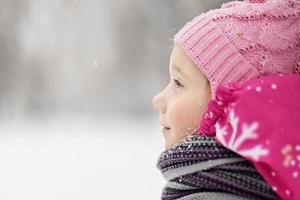 Portrait of a little girl in pink close-up. A child enjoys the snowfall. Christmas holiday photo
