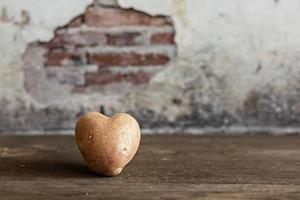 Heart shaped red potato on vintage background.The concept of farming, harvesting, vegetarianism. Valentine's Day. square, ugly food. photo
