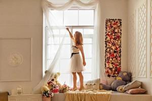Portrait of a young woman in a white dress straightening light white curtains by the window. photo