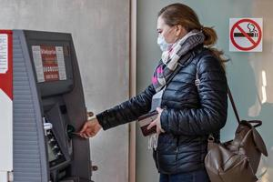 A woman wearing a protective medical mask on her face inserting a credit bank card and withdrawing cash from an ATM. photo
