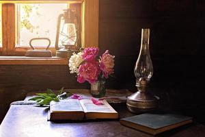 Bodegón de artículos vintage y un ramo de peonías en una mesa junto a la ventana en una antigua casa de pueblo. foto