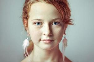 Close-up portrait of a young girl with festive makeup for a party. Valentine's Day. Earrings-feathers in the ears of the model photo
