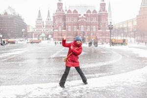 A beautiful young girl in a red jacket walks along Manezhnaya Square in Moscow during a snowfall and blizzard. Snowblowers are working in the background. photo