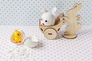 Wooden rabbit carrying a cart with an egg with bunny ears and a muzzle. Eggshell with a hatched chick. photo