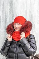 retrato de una mujer con un sombrero rojo y una bufanda, chaqueta cálida contra el fondo de una pared de hielo. invierno foto