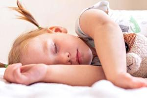 A little girl toddler is sleeping on a bed with toys cuddled . Childhood. photo