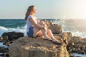 A young woman sits on the shore of the Mediterranean Sea at sunset photo